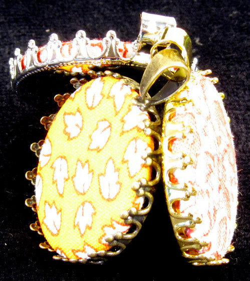 The pendant is shown with the inserts covered with fabric, but before the claws have been wrapped around the insert